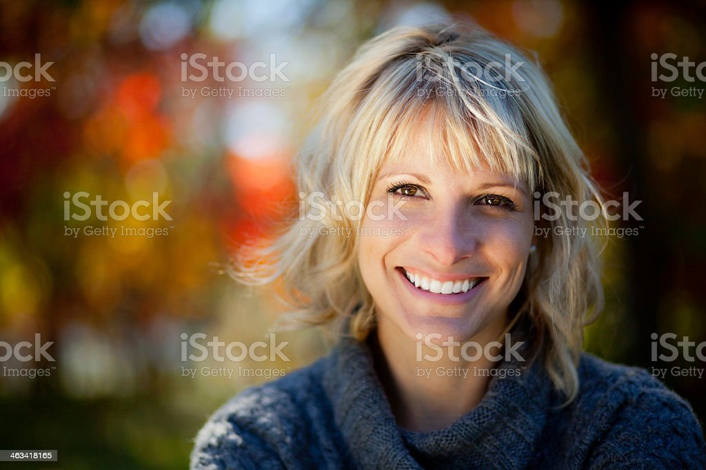 Mature blonde woman smiling with blurred fall scene stock photo