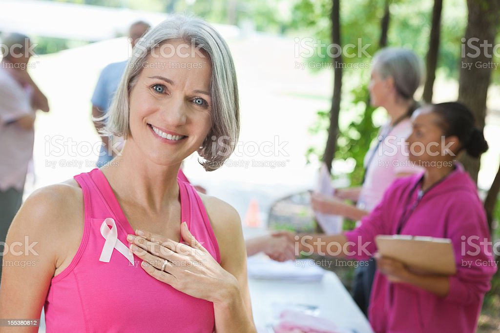 Mature breast cancer survivor signing up for outdoor charity race stock photo