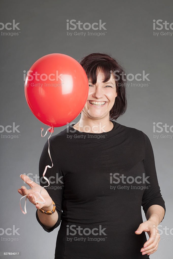 Mature brunette woman holding red balloon against gray background stock photo