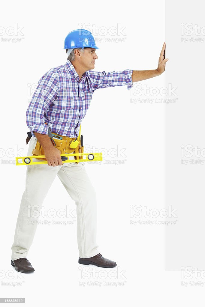 Mature builder with spirit level leaning on wall royalty-free stock photo