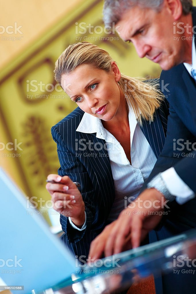 Mature business colleagues working on a laptop royalty-free stock photo