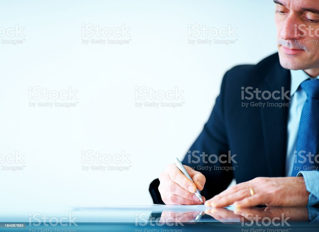 Mature business executive writing on papers at office desk royalty-free stock photo