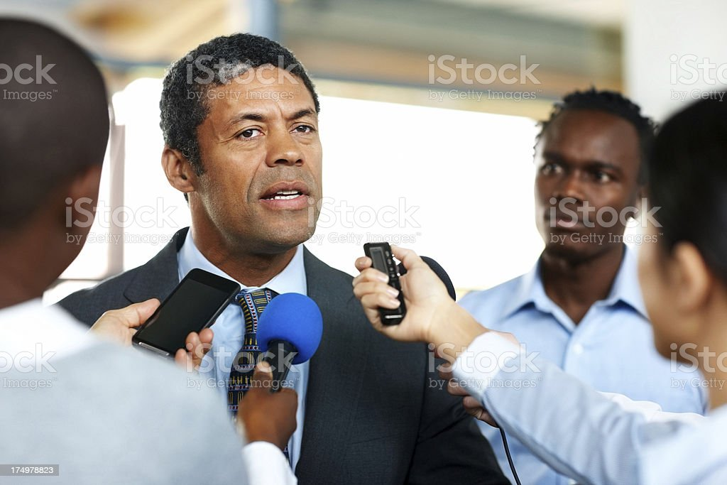 Mature business man answering to journalists royalty-free stock photo