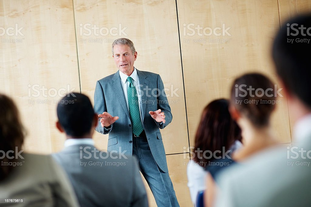 Mature business man discussing with his team at a seminar royalty-free stock photo