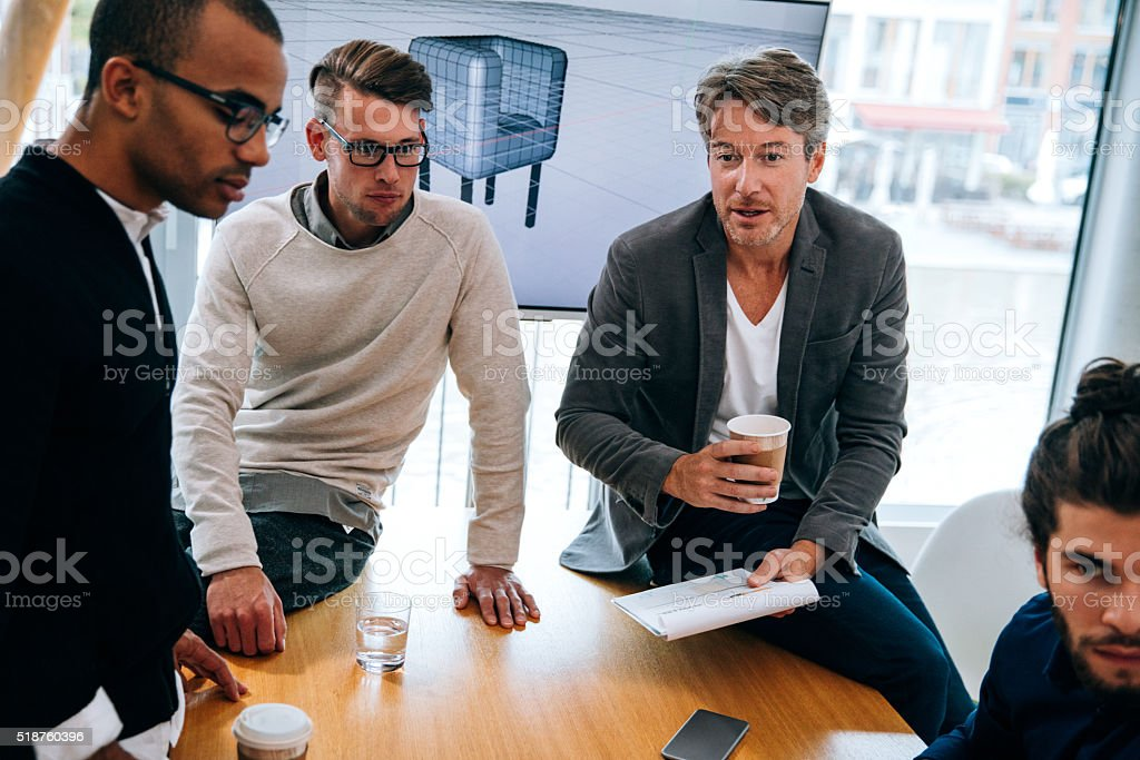 Mature business man giving notes to team from clipboard stock photo