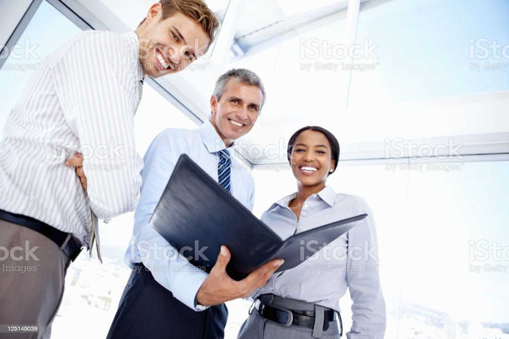 Mature business man holding folder with associates royalty-free stock photo