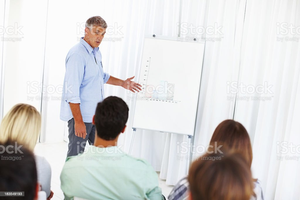 Mature business man presenting on white board royalty-free stock photo