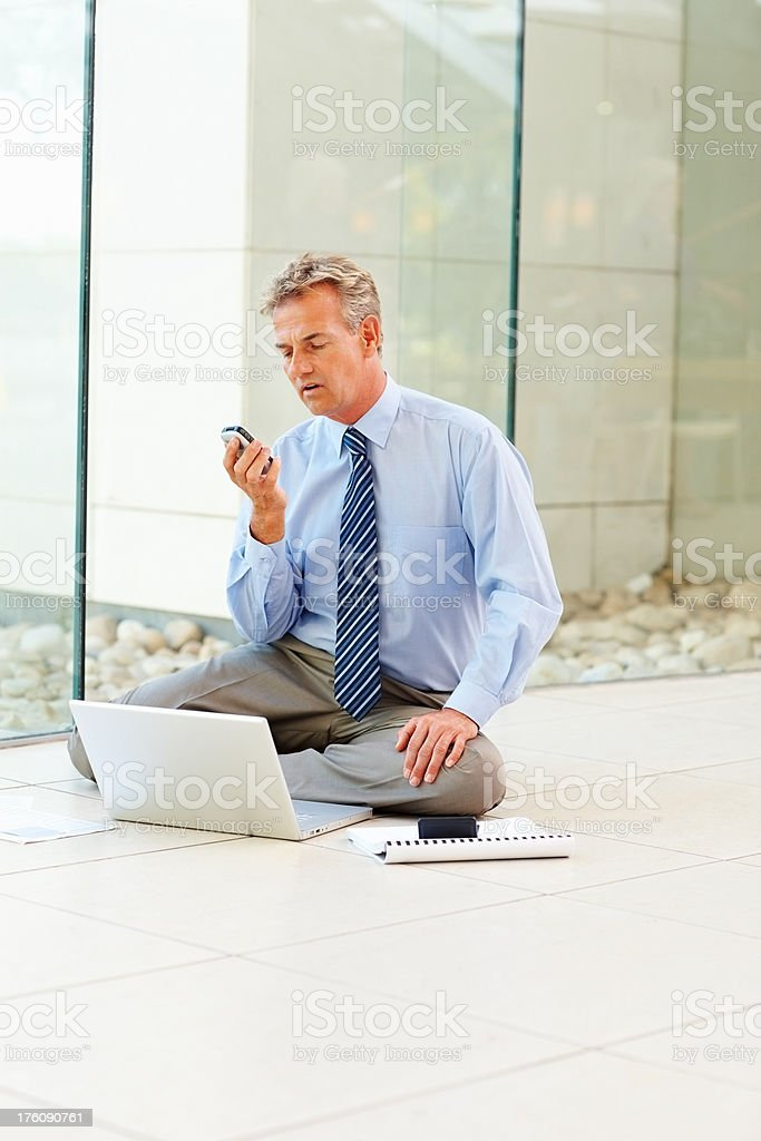 Mature business man reading message while working royalty-free stock photo