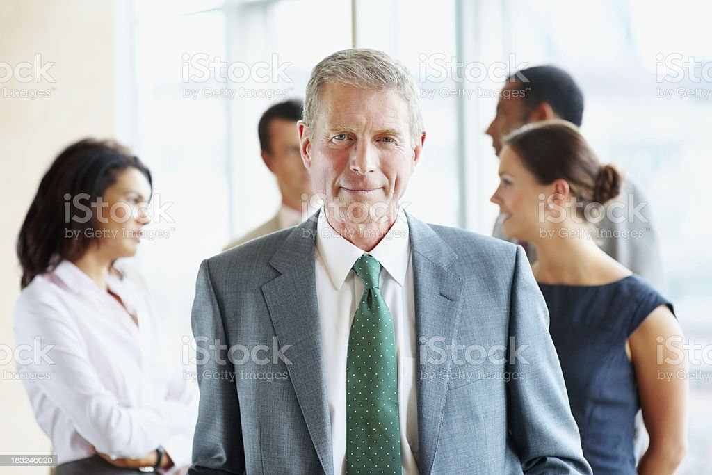 Mature business man with his team in background at office royalty-free stock photo