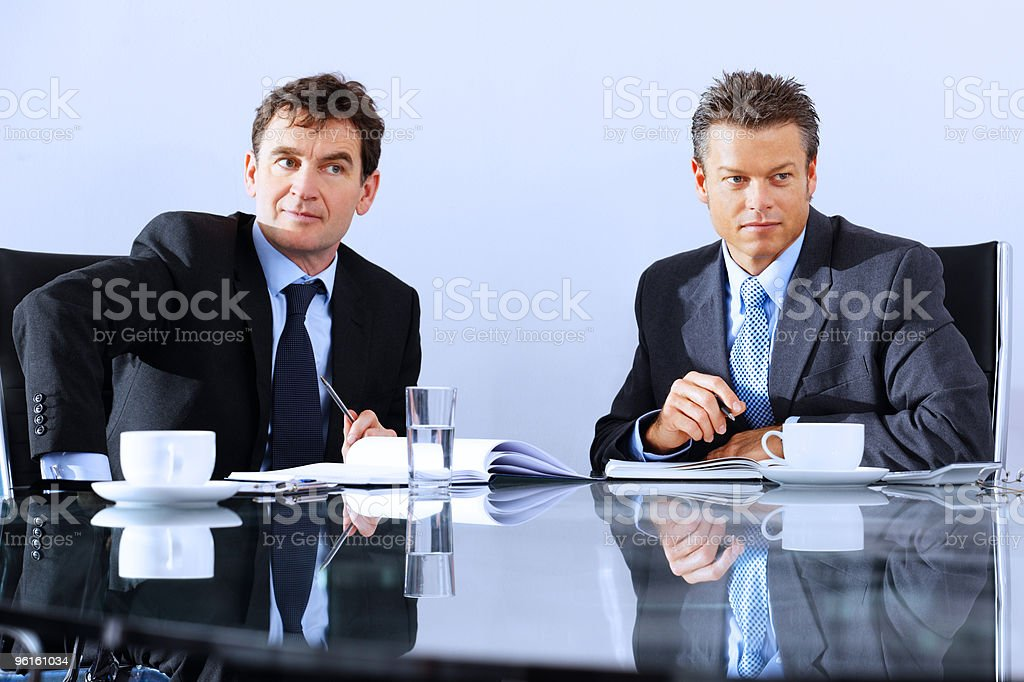 mature business men listening to colleague in a meeting stock photo