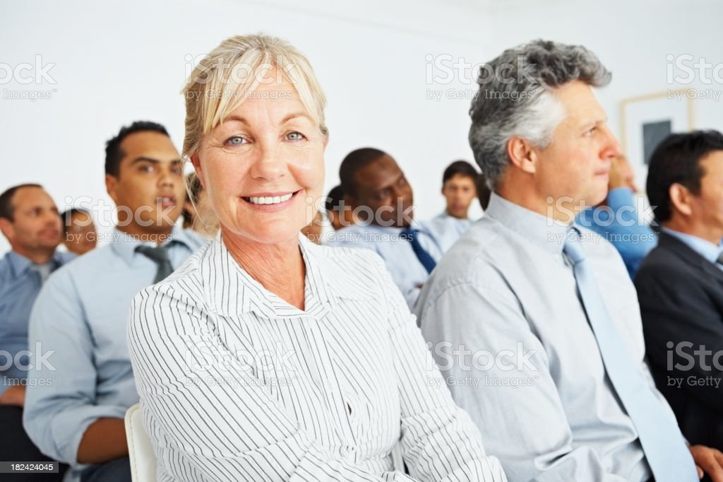 Mature business woman at a seminar with colleagues royalty-free stock photo