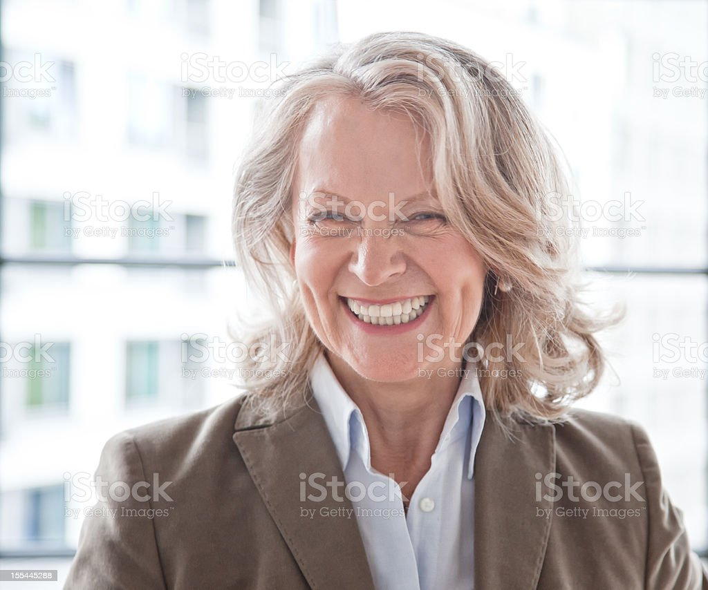 Mature business woman laughing in front of window, Berlin in...