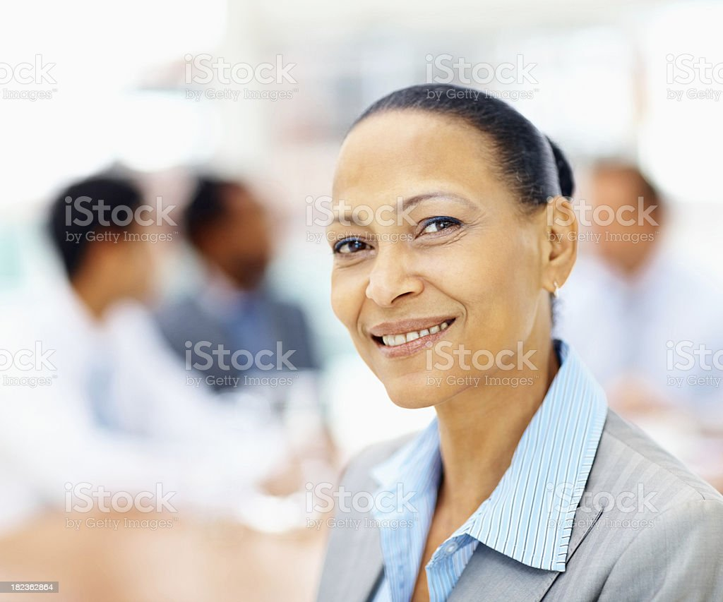 Mature business woman smiling with colleagues at the back royalty-free stock photo