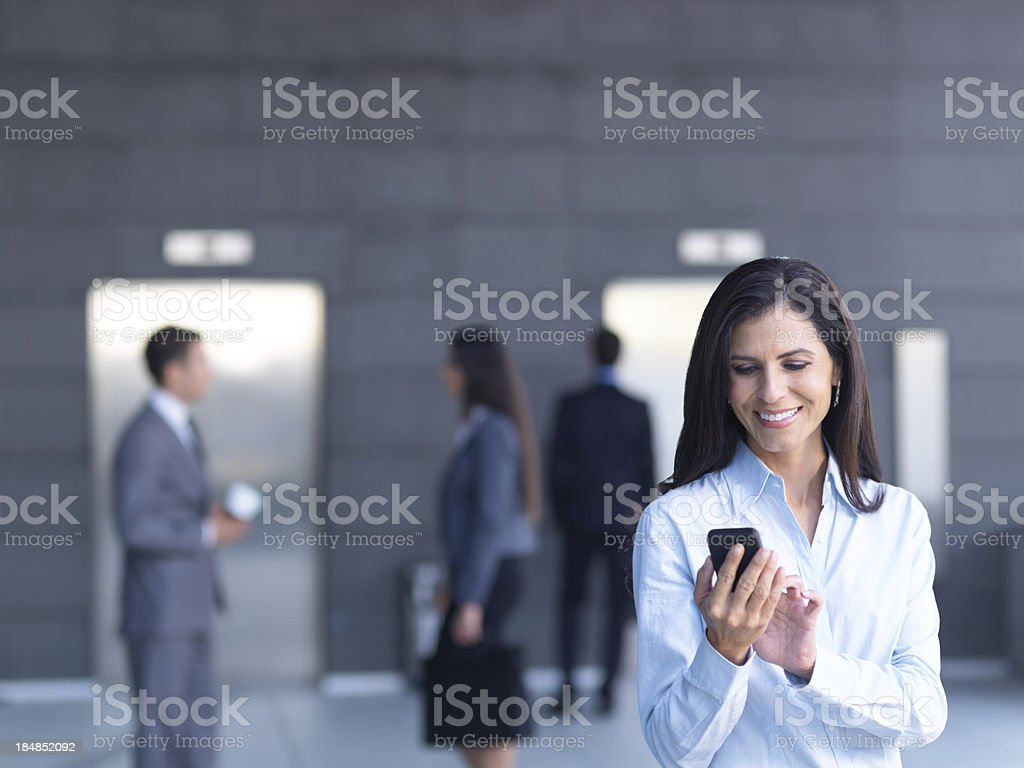 Mature business woman texting on cell phone royalty-free stock photo