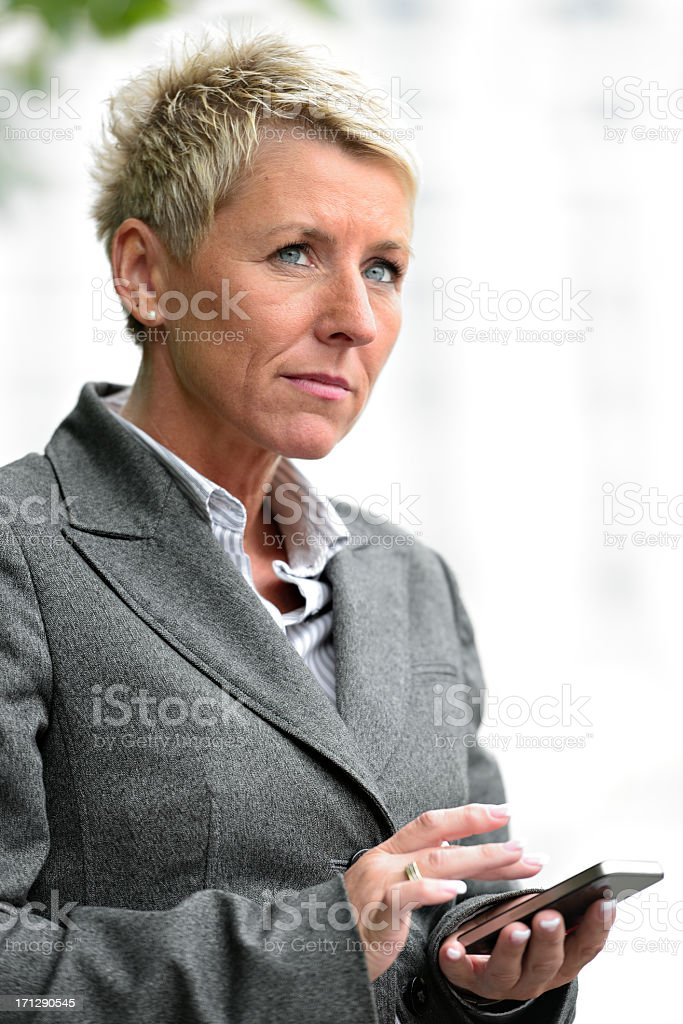Mature Business Woman Typing on Smartphone stock photo