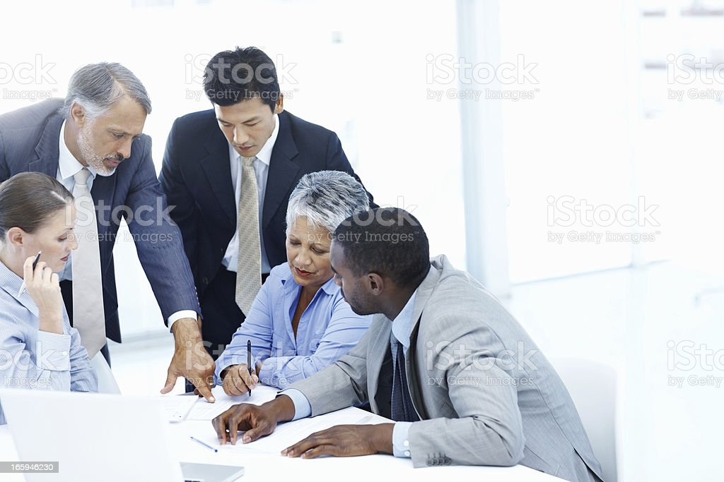 Mature business woman writing while conversing royalty-free stock photo