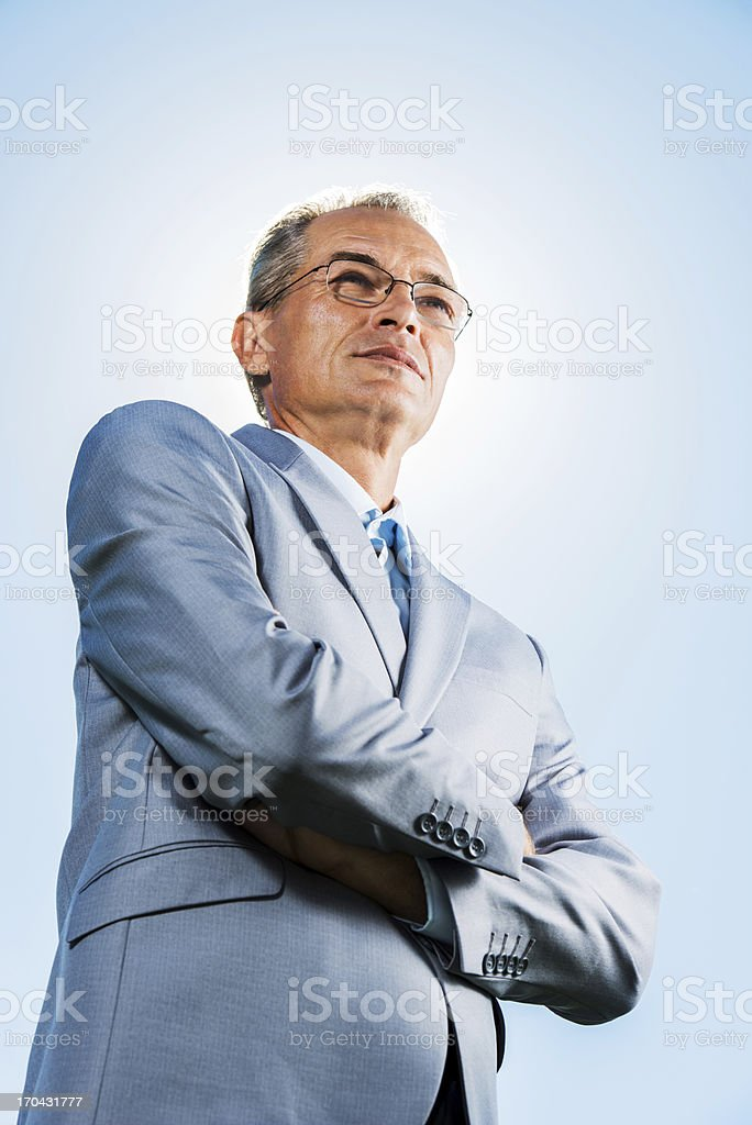Mature businessman against the blue sky. royalty-free stock photo