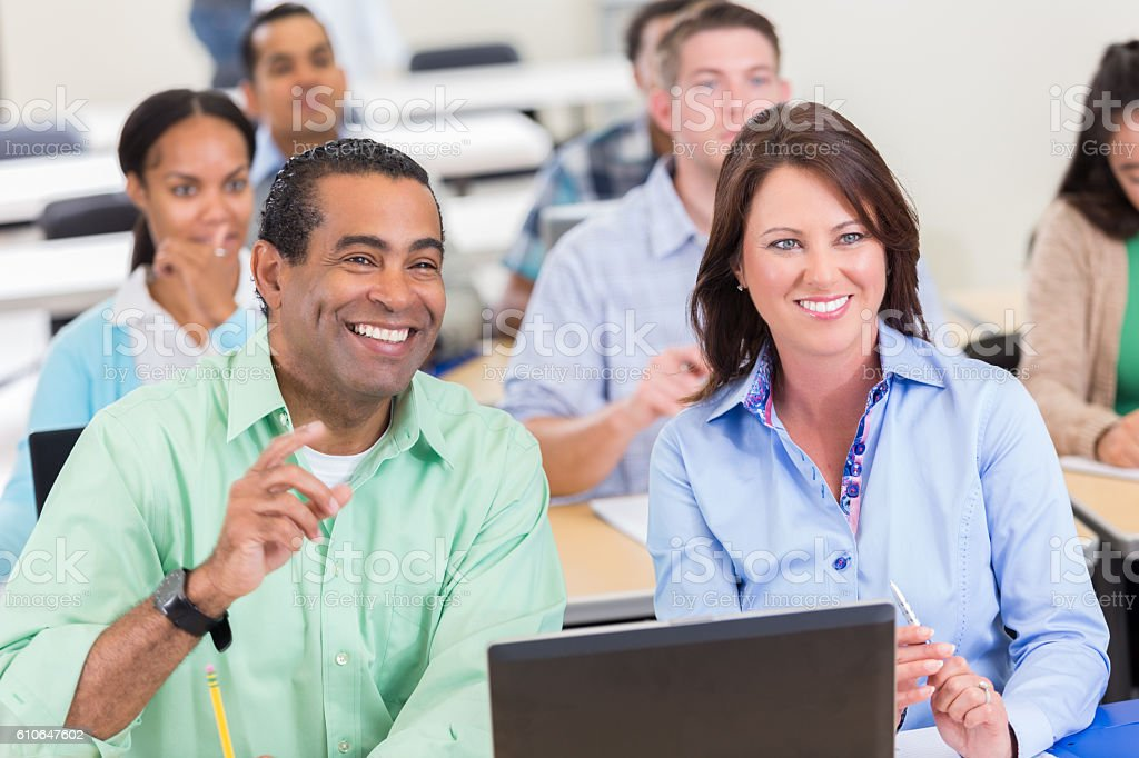 Mature businessman asks question during continuing education class stock photo