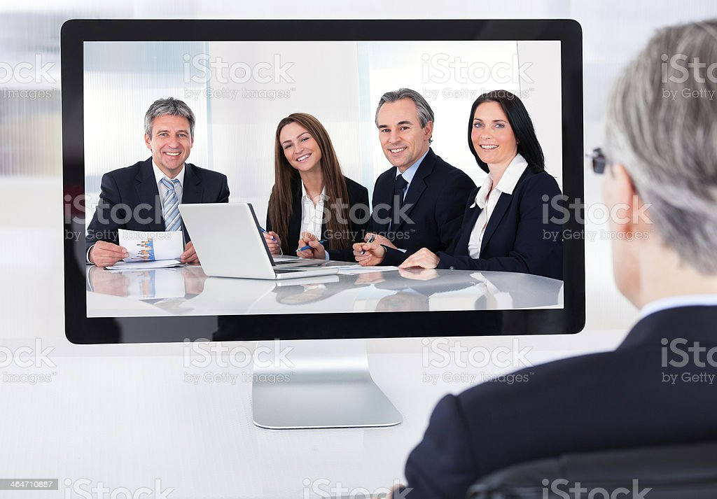 Mature businessman attending video conference stock photo