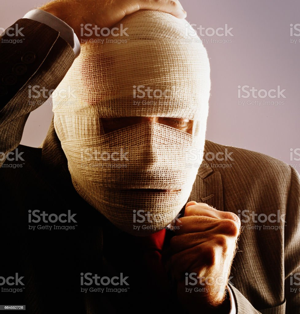 A middle-aged businessman, his face completely obscured by bandages,...