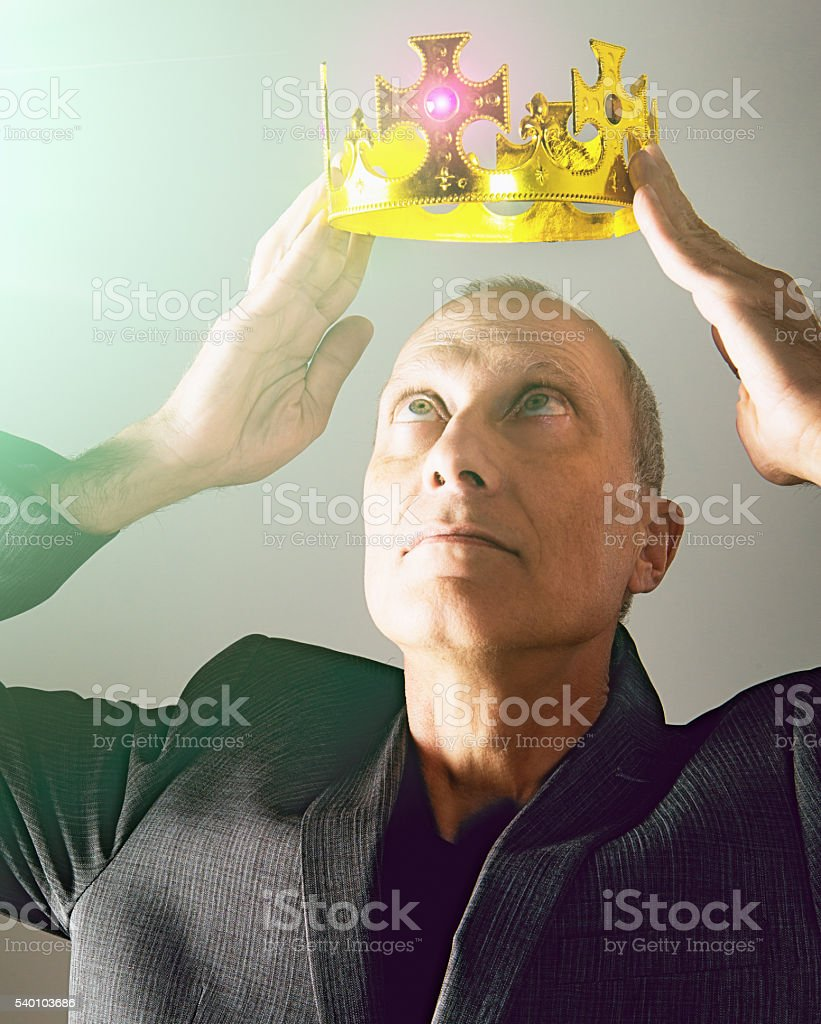 Mature businessman crowning himself triumphantly, obviously self centered stock photo