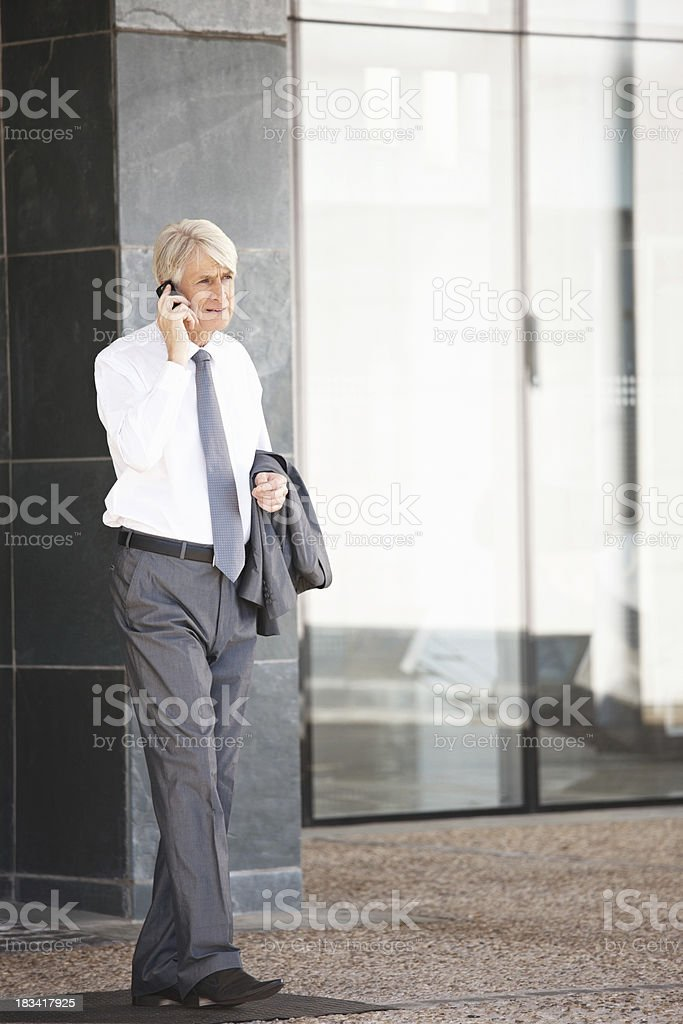 Mature businessman discussing on cell phone stock photo