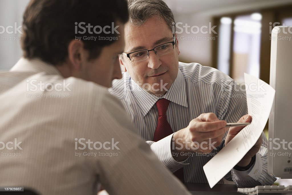 Mature businessman discussing report with younger colleague stock photo