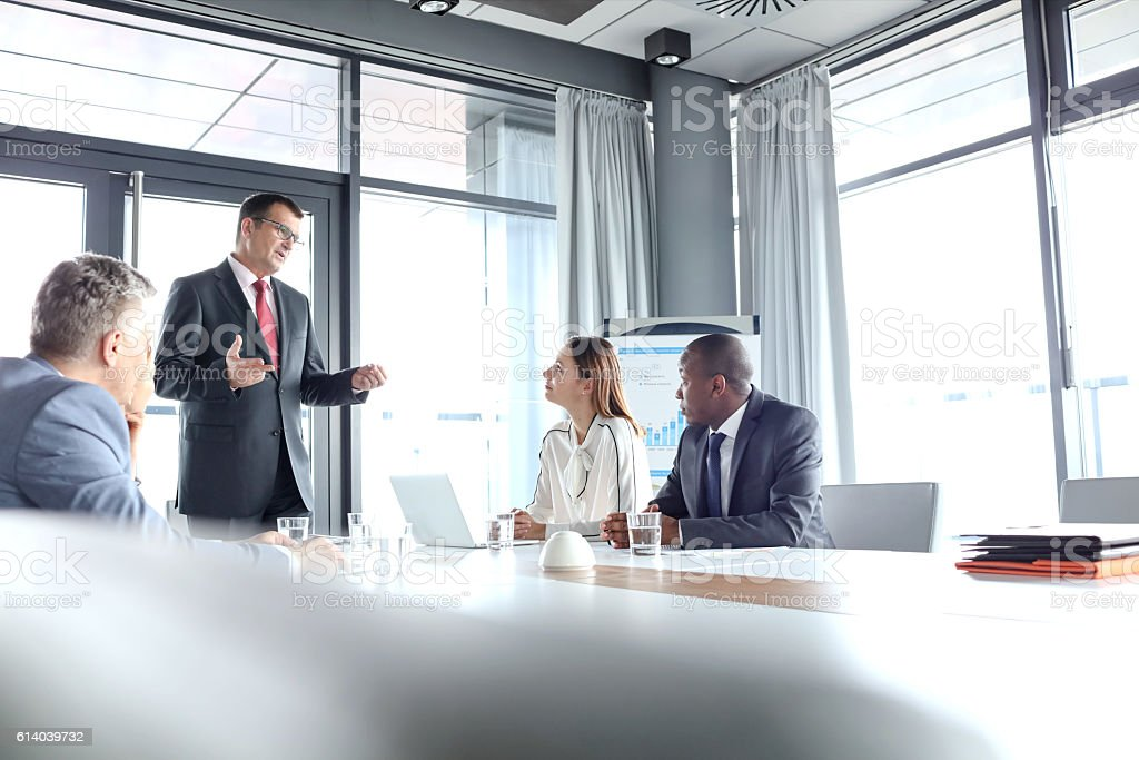 Mature businessman discussing with colleagues in board room stock photo