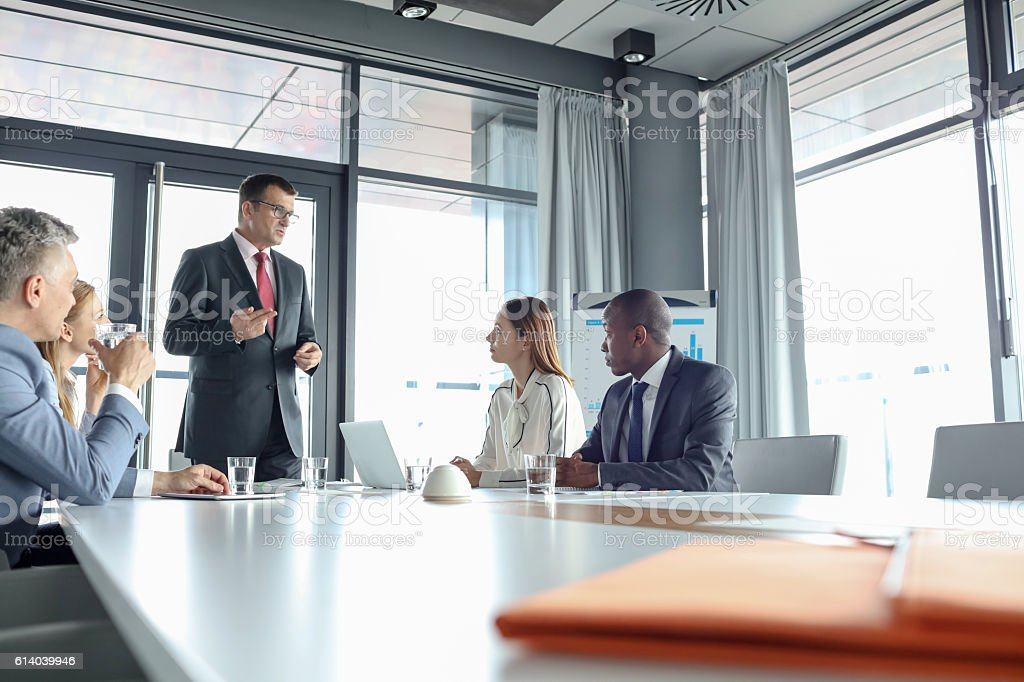 Mature businessman discussing with colleagues in meeting room stock photo