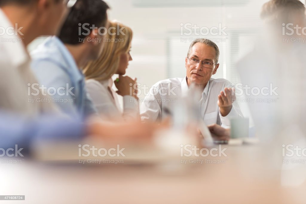 Mature businessman discussing with his colleagues on a meeting. stock photo