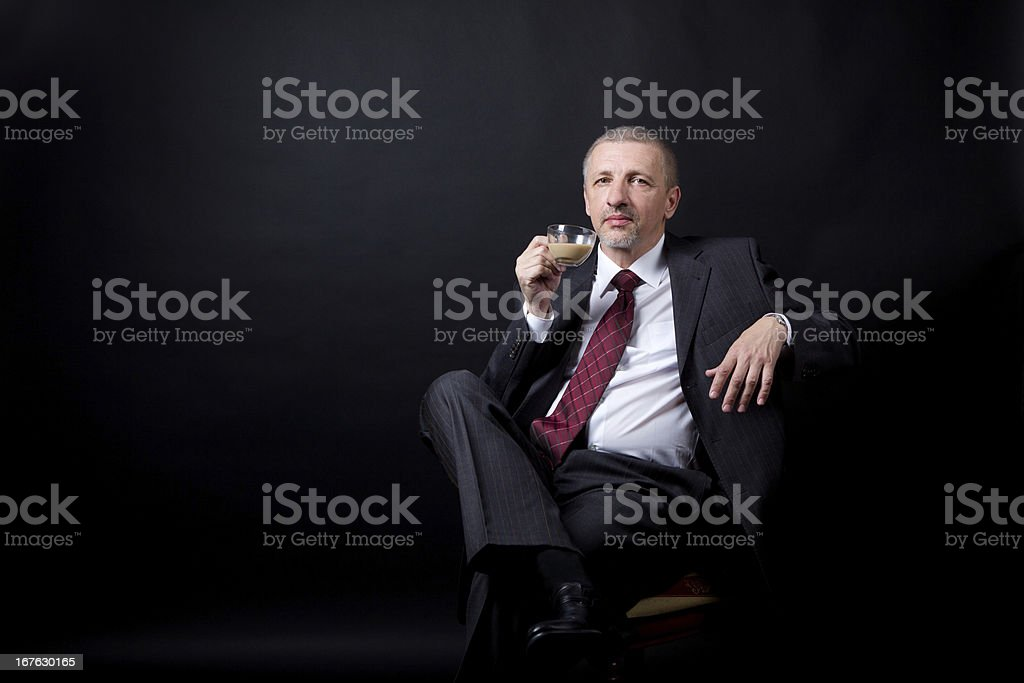 Mature businessman drinking coffee with milk royalty-free stock photo
