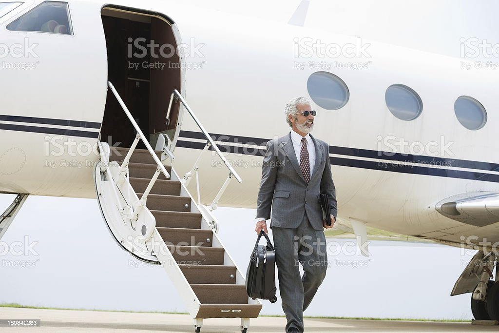 Mature businessman exiting private jet after flight stock photo