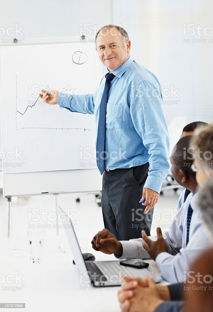 Mature businessman giving presentation to his colleagues royalty-free stock photo