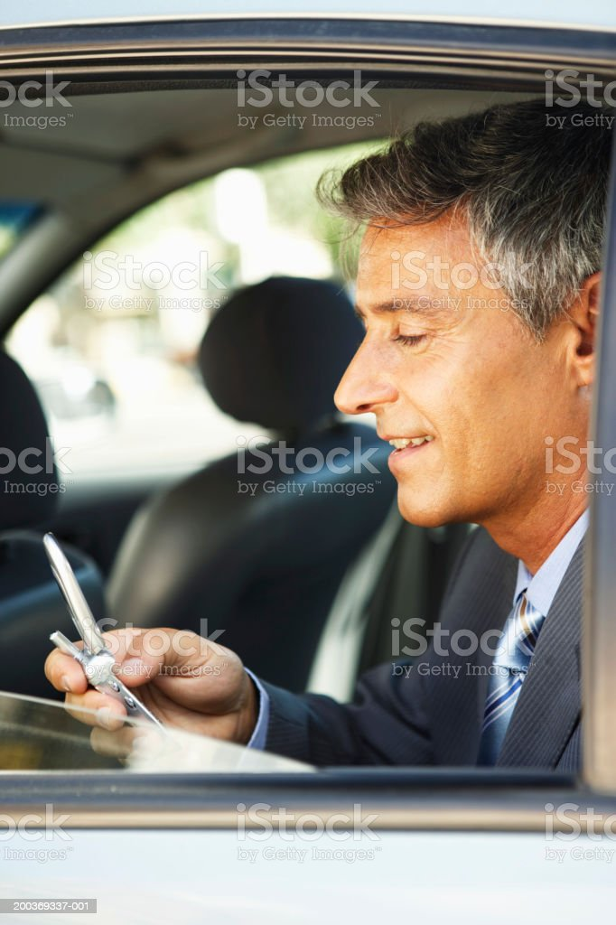 Mature businessman in back seat of car using mobile, side view royalty-free stock photo