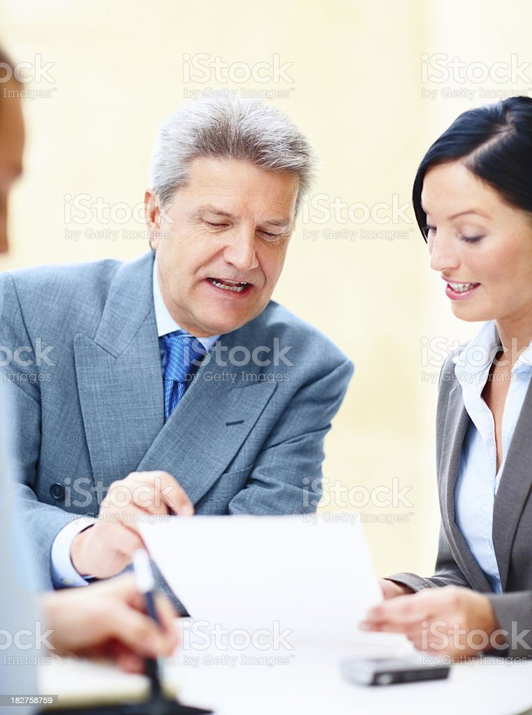 Mature businessman in discussion with his colleagues royalty-free stock photo