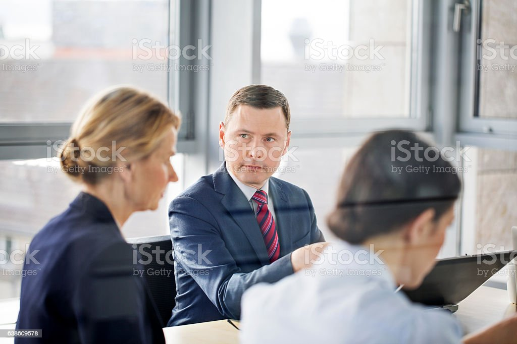 Mature businessman in meeting with colleagues stock photo