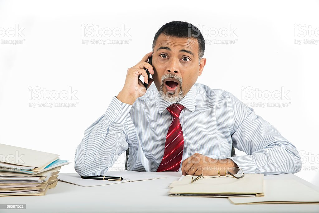 Mature businessman is surprised and shocked by phone message stock photo