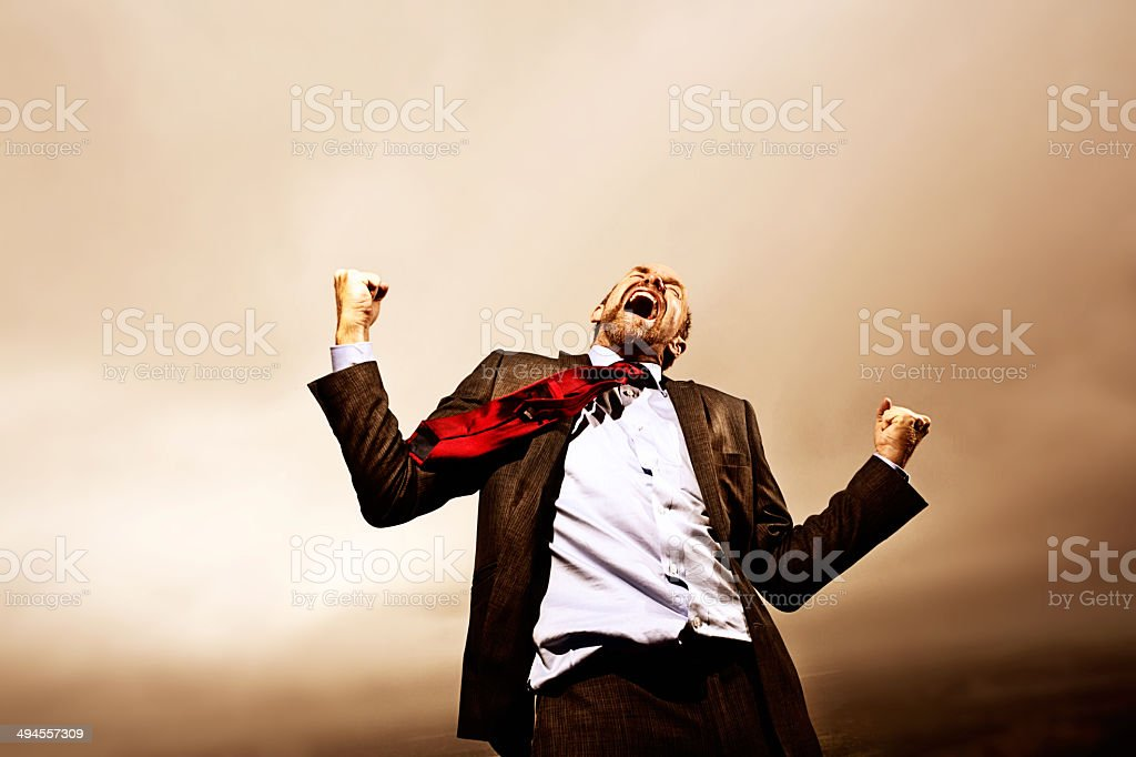 Mature businessman lets off steam, shouting defiantly in storm stock photo