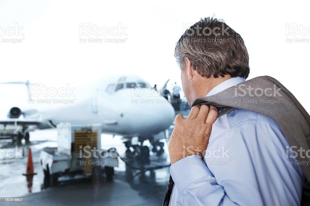 Mature businessman looking at aeroplane royalty-free stock photo