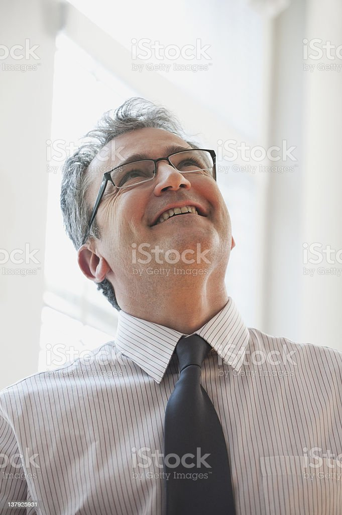 Mature businessman looking up smiling stock photo
