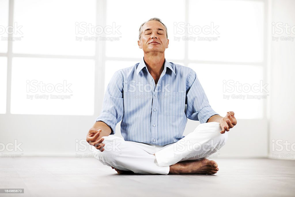 Mature businessman meditating at home. royalty-free stock photo