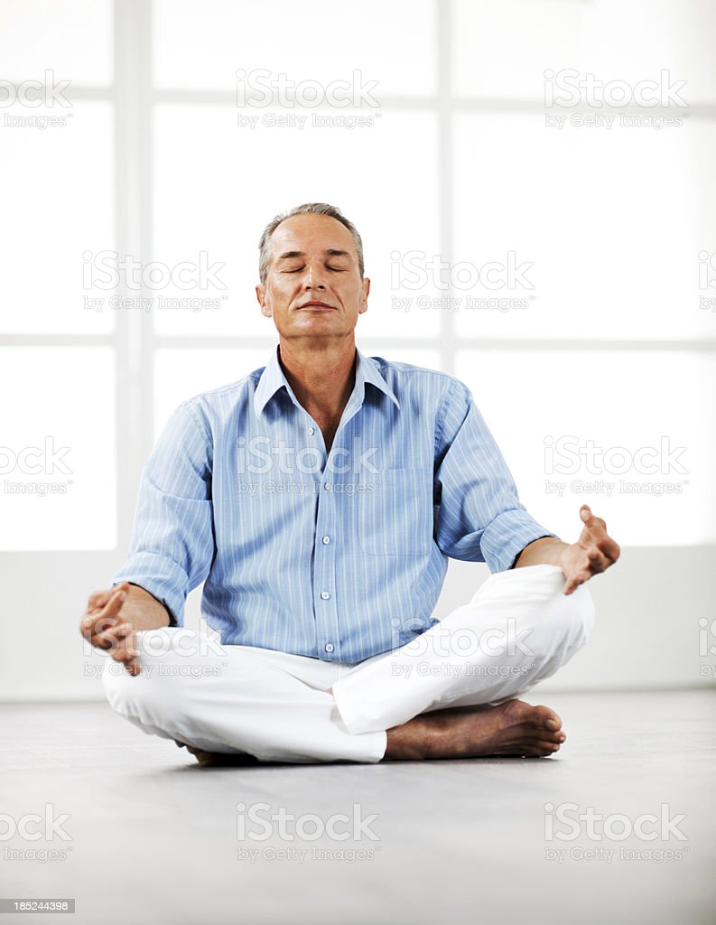 Mature businessman meditating at home. royalty-free stock photo