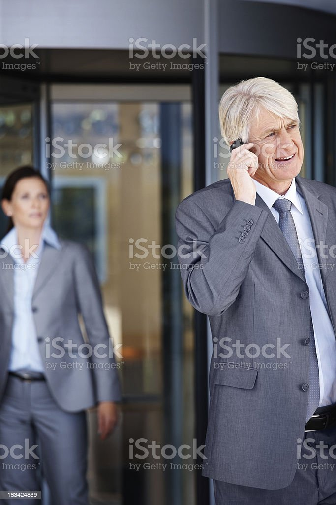 Mature businessman on phone with busines woman in background stock photo