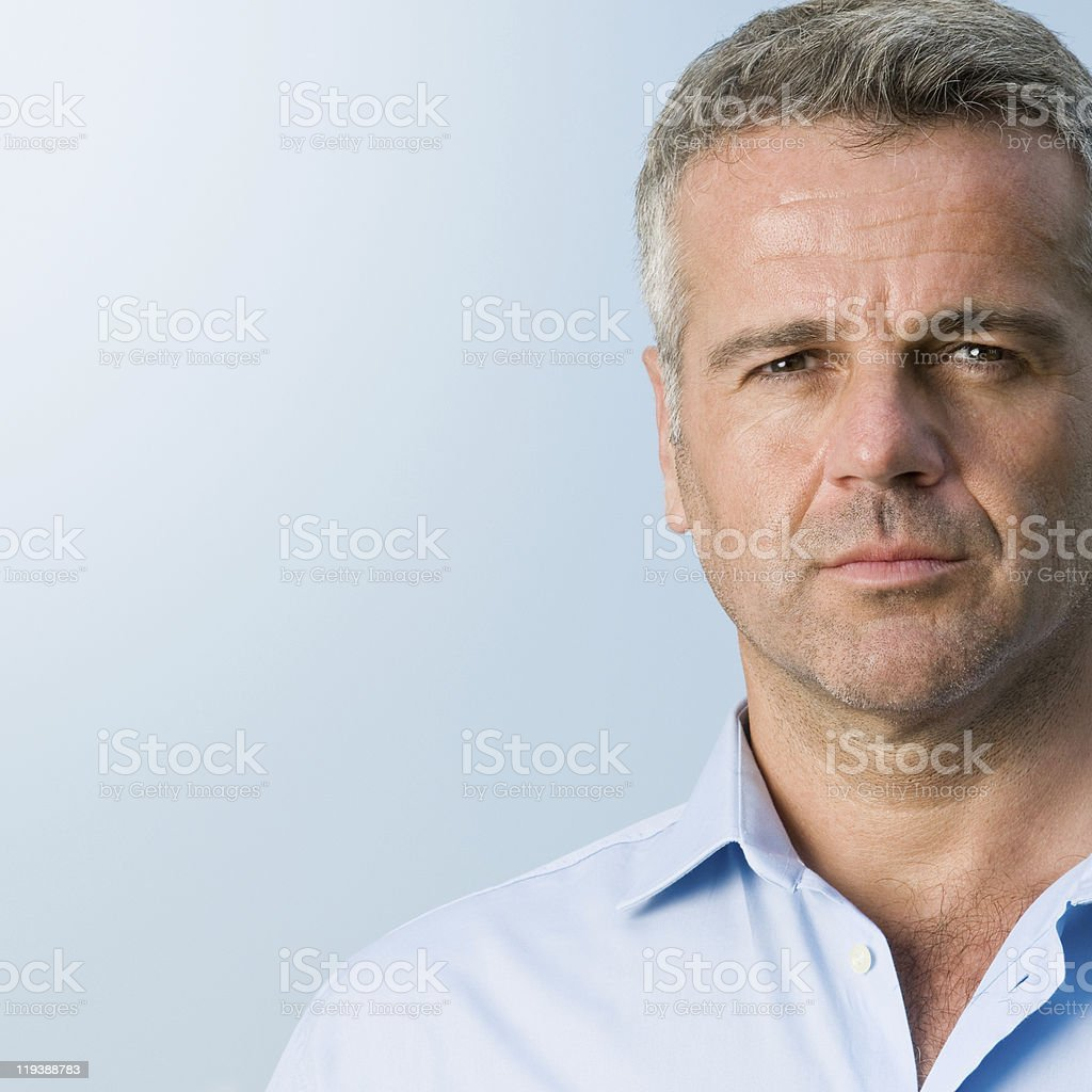 Mature businessman portrait against blue background stock photo