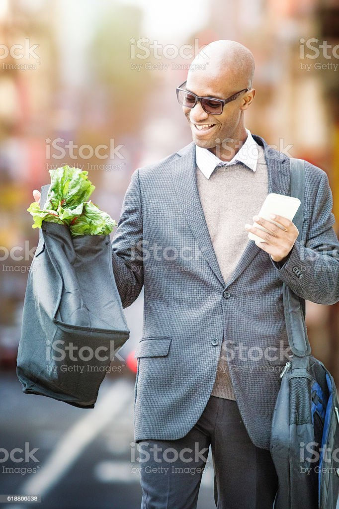 Mature businessman proud of his groceries commuting back home stock photo