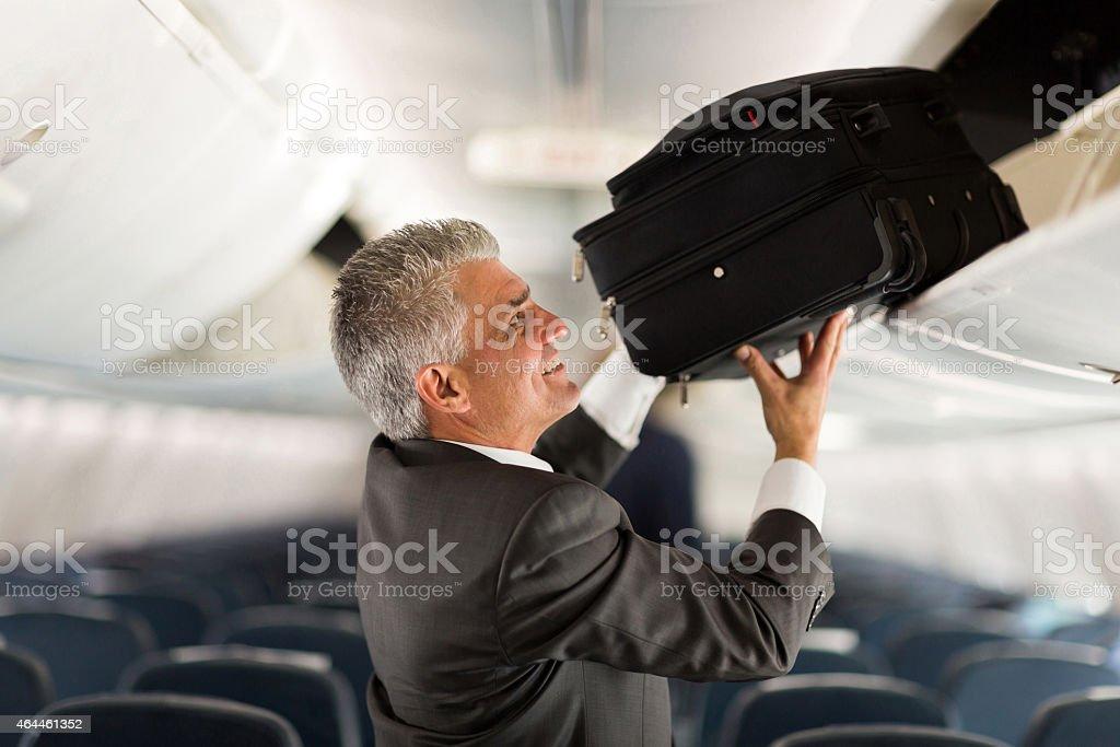 mature businessman putting luggage into overhead locker on airplane stock photo