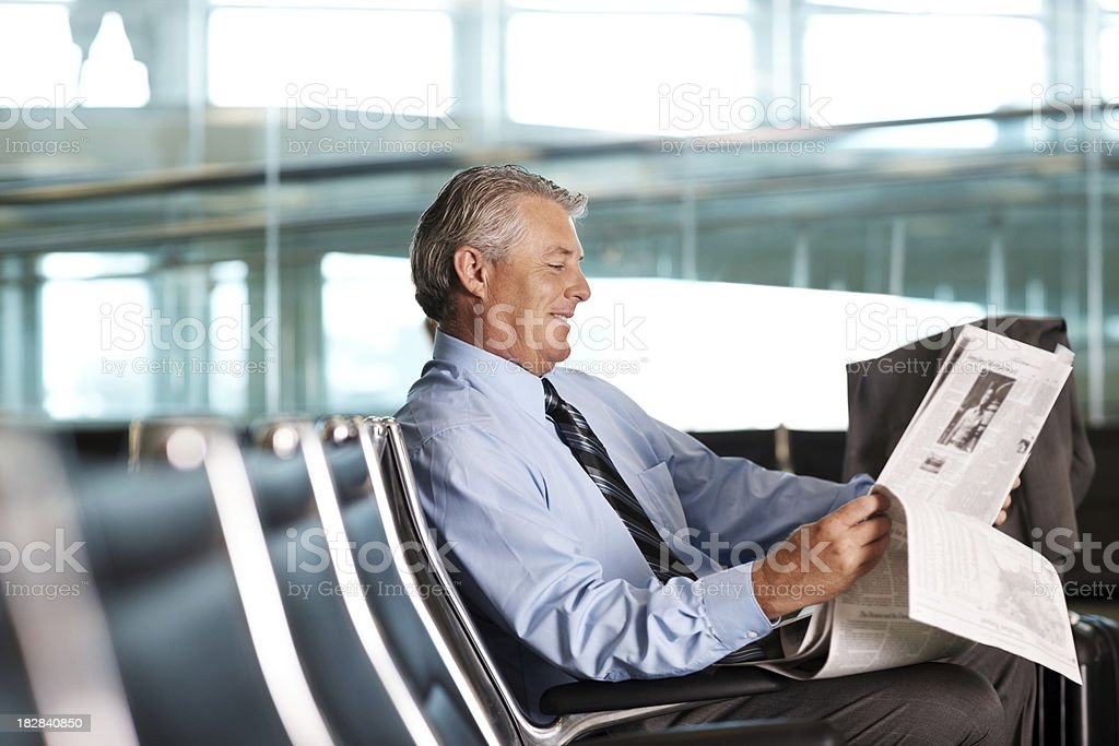 Mature businessman reading a newspaper at airport royalty-free stock photo