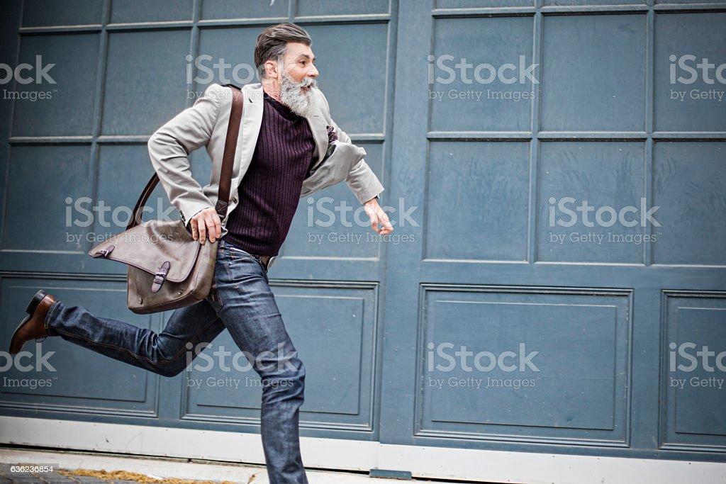 Mature businessman rushing to work stock photo