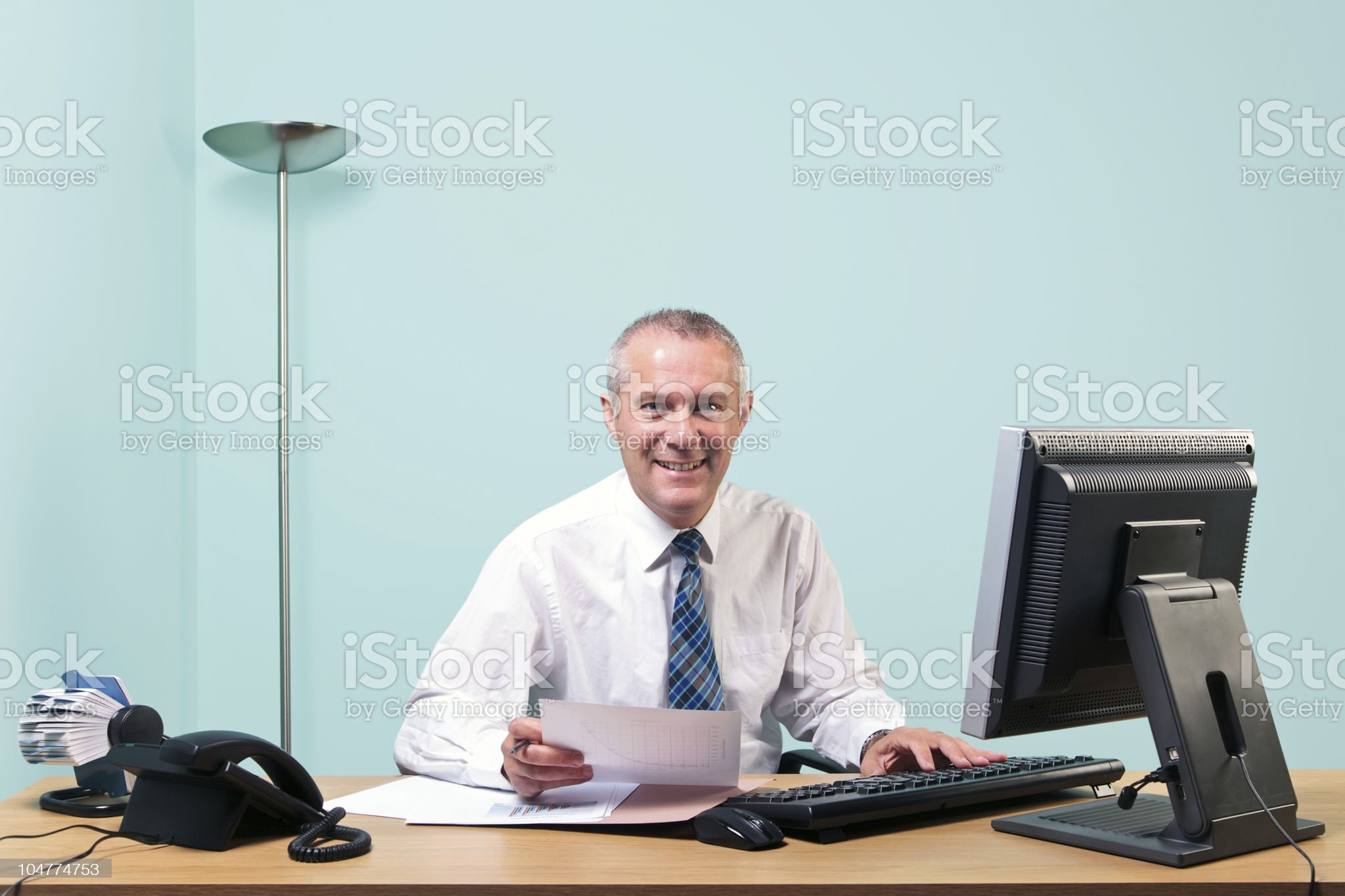 Mature businessman sat at his office desk royalty-free stock photo