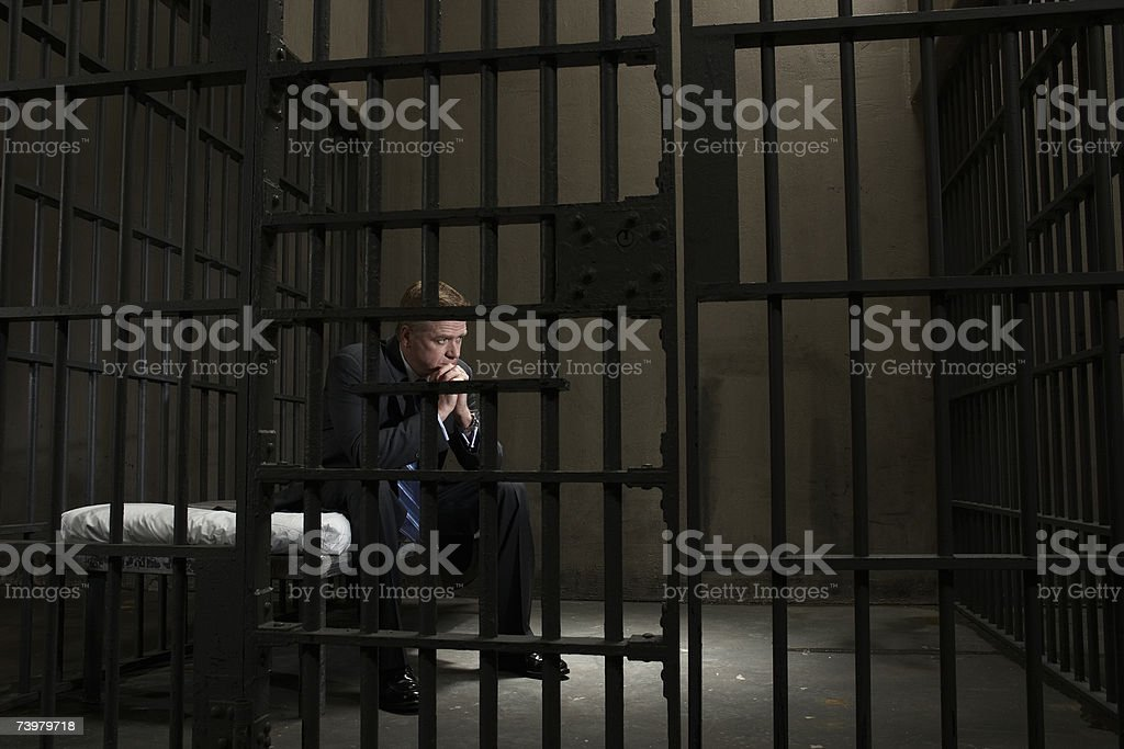 Mature businessman sitting on bed in prison cell stock photo